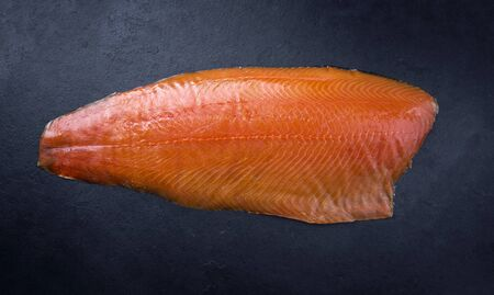 Traditional fresh graved salmon fillet offered as top view on a black board as background with copy space