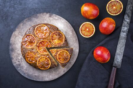 Traditional American upside-down bloody orange cake offered as closeup on a modern design plate Stock Photo