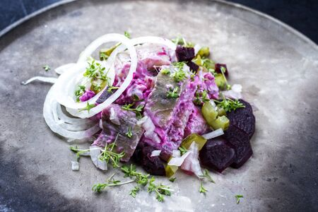 Traditional matie herring with beetroot salad and onion rings offered as closeup on a rustic modern design plate