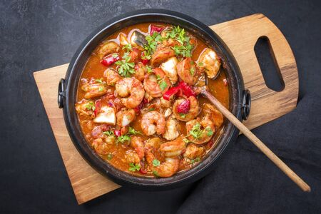 Traditional American fish stew cioppino with prawns, and fish as top view in a modern design cast-iron roasting dish