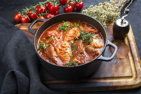 Traditional Brazilian fish stew moqueca baiana with fish filet in tomato sauce as closeup in a modern design cast-iron roasting dish  Stock Photo