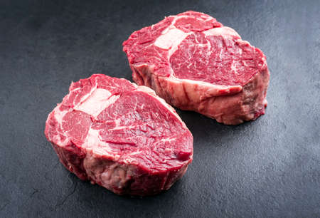 Raw dry aged wagyu Rib-Eye beef steak as closeup on a black background with copy space