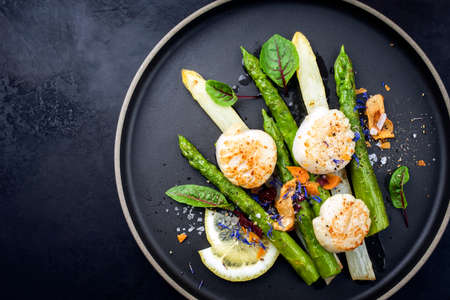 Traditional barbecue scallops with green and white asparagus offered as top view on a modern design plate with copy space left