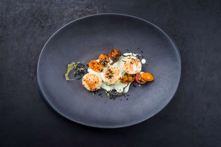 Traditional barbecue scallops with tomatoes, algae and Japanese furikake spice mix in a lemon coconut sauce offered as top view on a modern design plate with copy space