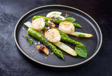 Traditional barbecue scallops with green and white asparagus offered as close-up on a modern design plate