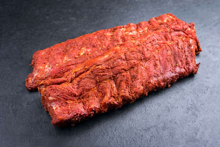 Raw pork spare loin ribs St Louis cut with spicy rub offered as closeup on black background with copy space