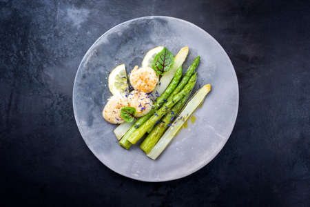 Traditional barbecue scallops with green and white asparagus as top view on a modern design plate with copy space