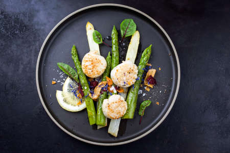 Traditional barbecue scallops with green and white asparagus offered as top view on a modern design plate with copy space Stok Fotoğraf