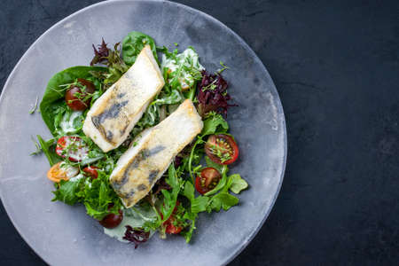 Traditional fried skrei cod fish filet with Italian lettuce and tomatoes in a lemon coconut sauce offered as top view in a modern design plate with copy space right