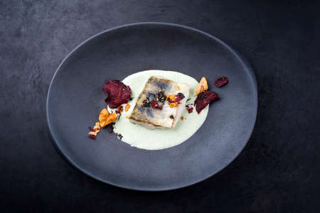 Traditional fried skrei cod fish filet with vegetable chips and algae in a lemon coconut sauce offered as top view in a modern design plate with copy space Stock Photo