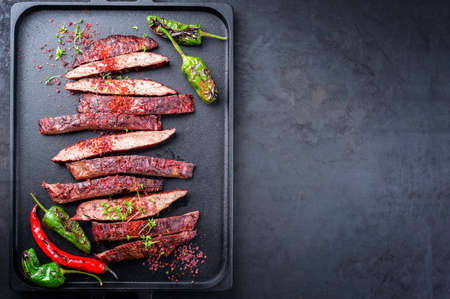 Traditional barbecue sliced dry aged wagyu flank steak offered with chili and paprika as top view on a modern design cast iron tray with copy space right