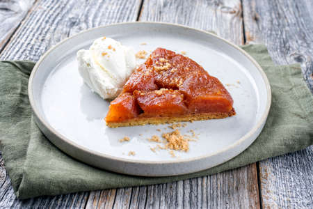 Traditional French tarte tatin with apples and ice cream offered as close-up on a modern Nordic design plate with rustic background