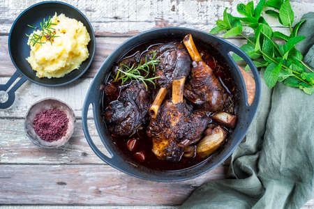 Modern style traditional braised slow cooked lamb shank in red wine sauce with shallots and mashed potatoes offered as top view in a design stewpot Banco de Imagens
