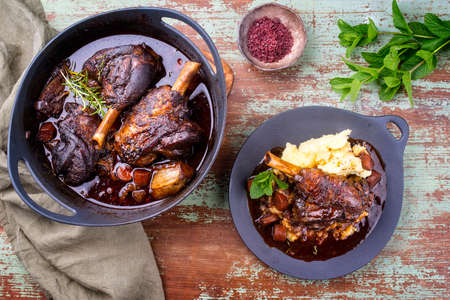 Modern style traditional braised slow cooked lamb shank in red wine sauce with shallots and mashed potatoes offered as top view on a design cast iron plate and pot Banque d'images