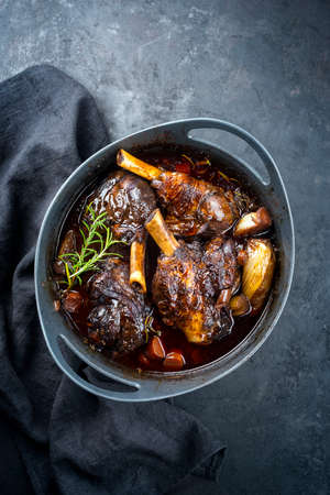 Modern style traditional braised slow cooked lamb shank in red wine sauce with shallots and carrots offered as top view in a design stewpot with copy space Banco de Imagens