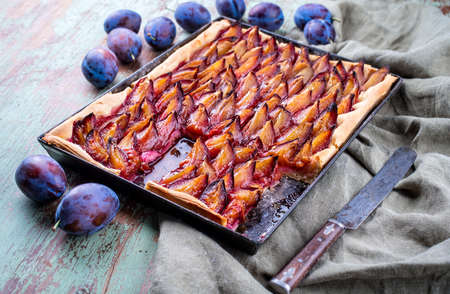 Traditional German Zwetschgenkuchen with sliced plums offered as close-up on a rustic backing sheet on a wooden board