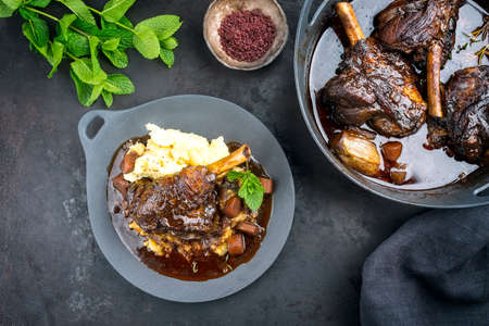 Modern style traditional braised slow cooked lamb shank in red wine sauce with shallots and mashed potatoes offered as top view on a design cast iron plate and pot