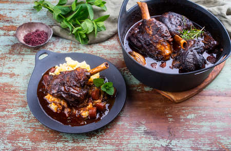 Modern style traditional braised slow cooked lamb shank in red wine sauce with shallots and mashed potatoes offered as close-up in a design cast iron plate Banco de Imagens