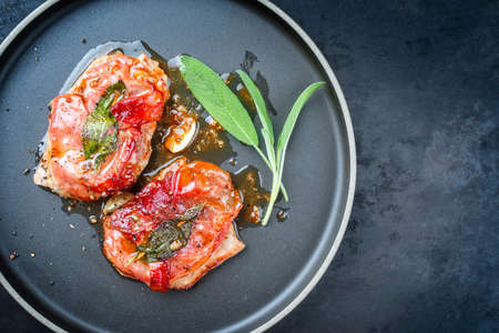 Modern style traditional Italian fried pork saltimbocca alla Romana with Parma ham and sage leaves offered as top view in a Nordic design plate with copy space right