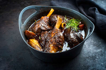 Modern style traditional braised slow cooked lamb shank in red wine sauce with shallots and carrots offered as close-up in a design stewpot