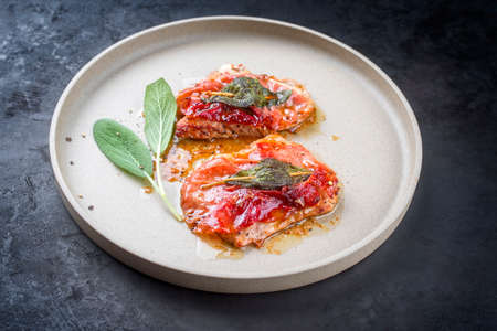 Modern style traditional Italian fried pork saltimbocca alla Romana with Parma ham and sage leaves offered as close-up in a Nordic design plate with copy space