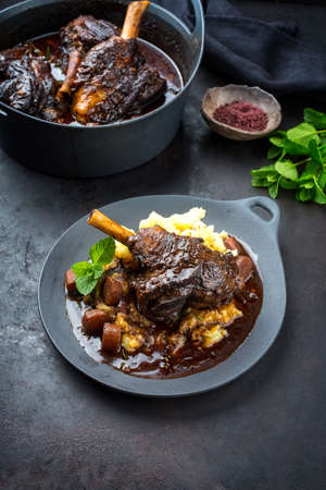 Modern style traditional braised slow cooked lamb shank in red wine sauce with shallots and mashed potatoes offered as close-up on a design cast iron plate and pot