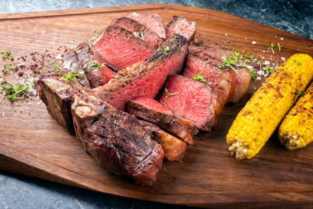 Modern style traditional barbecue dry aged wagyu porterhouse beef steak offered with corn and spice as close-up on modern design wooden board