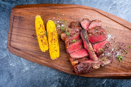 Modern style traditional barbecue dry aged wagyu porterhouse beef steak offered with corn and spice as top view on modern design wooden board