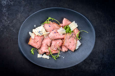 Modern style traditional lunch meat with sliced cold cuts roast beef with rocket salad and parmesan cheese offered as top view in a modern design plate