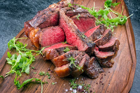 Modern style traditional barbecue dry aged wagyu porterhouse beef steak offered with lettuce and spice as top view on modern design wooden board