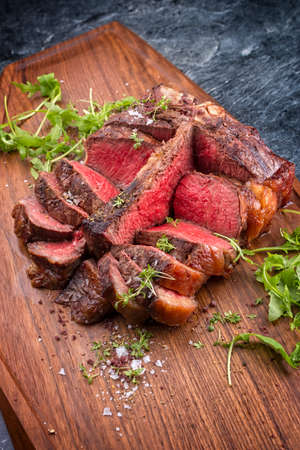 Modern style traditional barbecue dry aged wagyu porterhouse beef steak offered with lettuce and spice as close-up on modern design wooden board