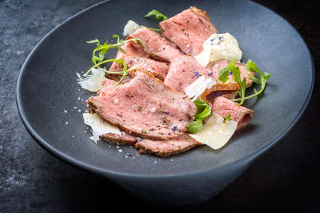 Modern style traditional lunch meat with sliced cold cuts roast beef with rocket salad and parmesan cheese offered as close-up in a modern design plate Фото со стока