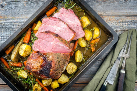 Traditional corned pot pork roast sliced and offered with potatoes, carrots and fennel in clear sauce as top view on a rustic metal tray