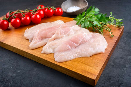 Raw traditional chicken escalope with tomatoes and herbs offered as close-up on a modern design wooden board with copy space