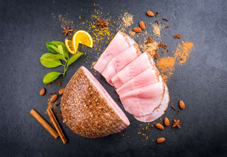Modern style traditional German boiled Christmas ham with exotically spices and orange offered as top view on a black board