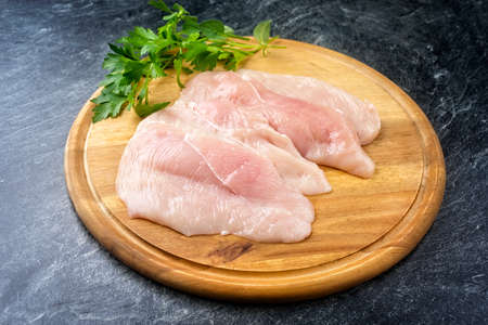 Raw traditional chicken escalope with herbs offered as close-up on a rustic wooden cutting board copy space