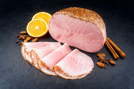 Modern style traditional German boiled Christmas ham with almond, cinnamon and orange offered as close-up on a black board with copy space