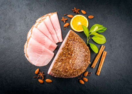 Modern style traditional German boiled Christmas ham with almond, cinnamon and orange offered as top view on a black board with copy space Фото со стока