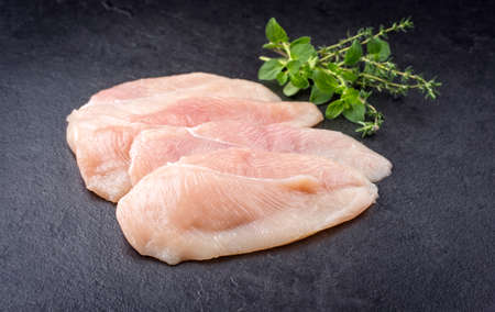 Raw traditional chicken escalope filets with herbs offered as close-up on a black board with copy space