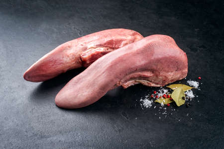 Traditional cooked beef tongue with spice offered as close-up on a rustic black board