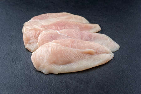 Raw traditional chicken escalope filets offered as close-up on a black board with copy space