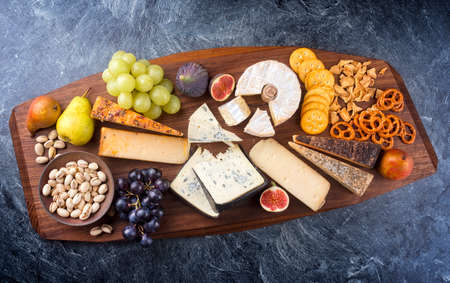 Modern style traditional party platter with soft cheese, fruits and snacks as top view on a wooden design board