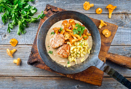 Modern style traditional barbecue pork filet medaillons in cream sauce with chanterelle mushrooms and spaetzle offered as top view on a rustic wrought iron skillet