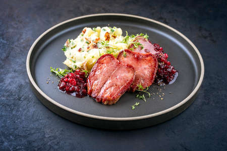 Traditional fried cured and sliced veal tongue with mashed potatoes and cranberries relish offered as close-up in a Nordic design plate