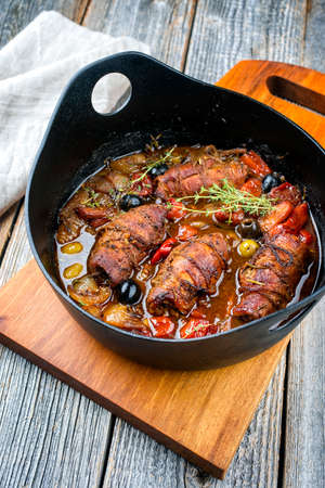 Modern style traditional slow cooked German beef roulades with vegetable and olives in spicy gravy sauce as close-up in a design pot