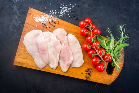 Raw traditional chicken escalope with tomatoes and herbs offered as top view on a modern design wooden board with copy space