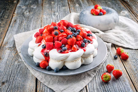 Modern style traditional Australian Pavlova torte with meringue cream and fruits offered as close-up on a design plate