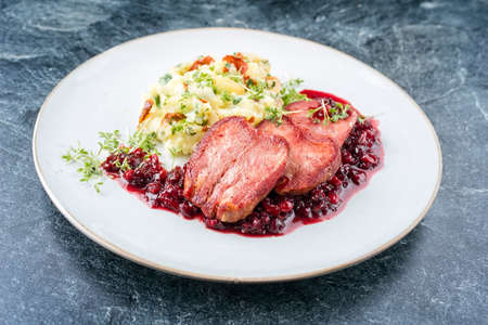 Traditional fried cured and sliced veal tongue with mashed potatoes and cranberries relish offered as close-up on a classic design plate Фото со стока