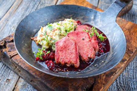 Traditional fried cured and sliced veal tongue with mashed potatoes and cranberries relish offered as close-up in a rustic wrought-iron skillet on a wooden board