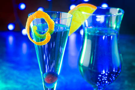 Traditional cocktail volcano with blue curacao and champaign offered as close-up in design glasses